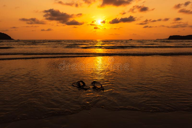 Pair of flip flops at sunset, sunrise time on the beach. Pair of flip flops at sunset time on the beach royalty free stock image