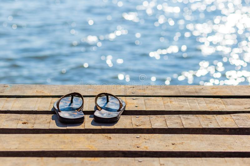 Pair of flip flops on the wooden dock and scenery of lake river at natural background. Pair of flip flops on the wooden dock and scenery of lake river royalty free stock photos