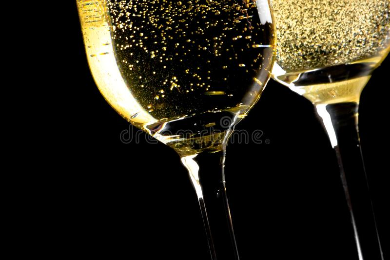A pair of flutes of champagne tilted with golden bubbles. On black background and space for text royalty free stock photography