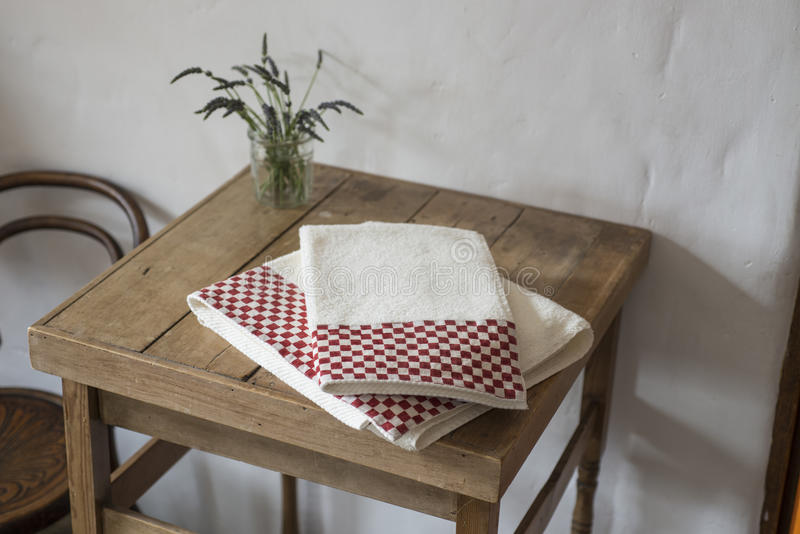 Pair of Folded Hand Towels on Small Wooden Table. A couple of folded hand towels with maroon checkerboard pattern on edges placed on top of small wooden table stock photos