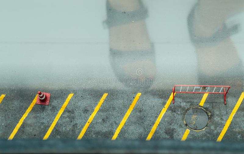 Street signs and reflections. Pair of foot reflected on the window glass showing road safety signs stock photos