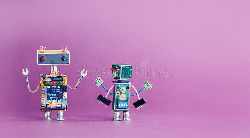 Pair funny robots characters on pink violet background. 4 industrial revolution concept. Cyber toys hand up. Copy space stock photography
