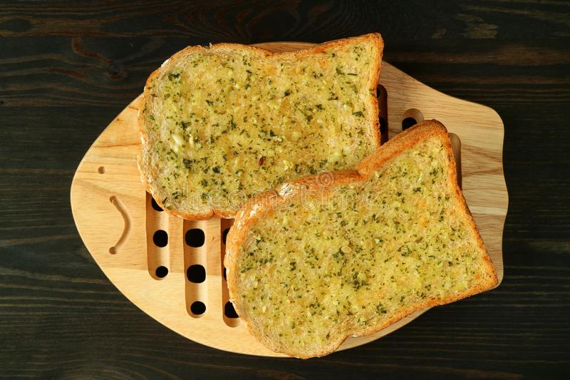 Pair of Garlic Butter Toasts on Wooden Plate Served on Dark Color Background. Food texture appetizer baked beige bread break breakfast brown closeup coffee cut stock photography