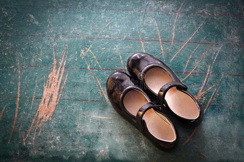 Pair of Girl Shoes on old blackboard. Back to school concept stock image