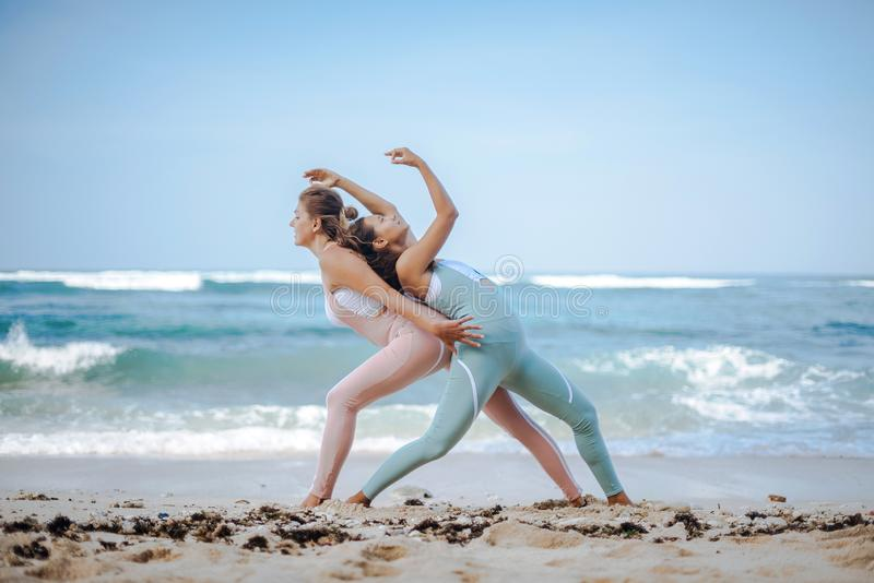 Pair of girls practice yoga against the background of the ocean royalty free stock images