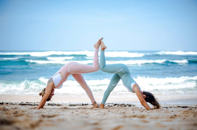 Pair of girls practice yoga against the background of the ocean stock images
