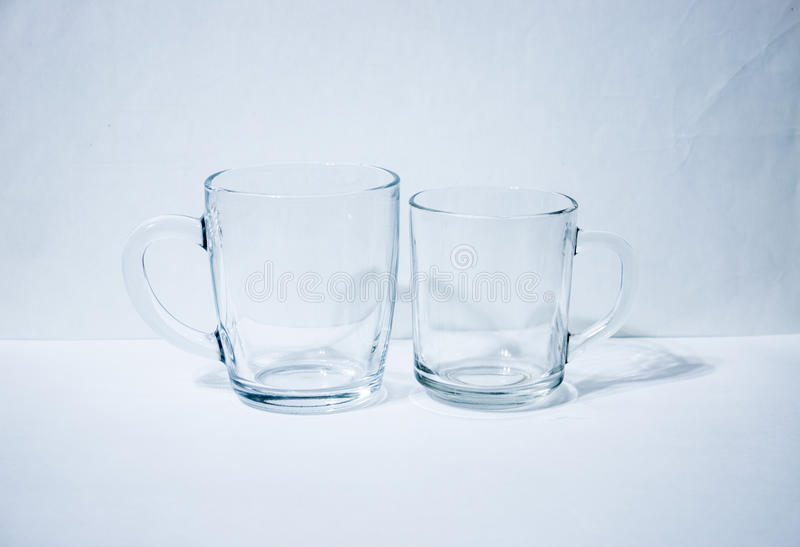 Pair of glass beakers. Light background royalty free stock image