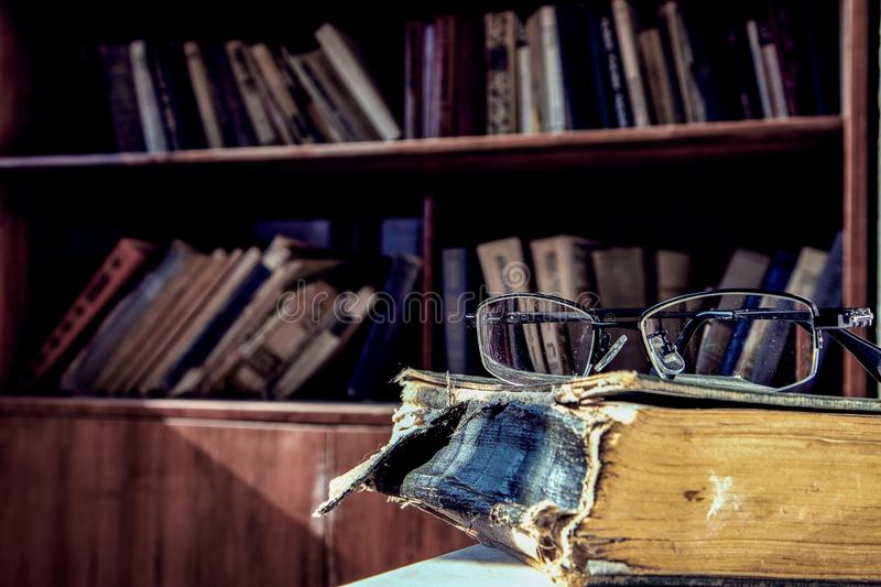 Pair of glasses on an ancient history book in the library with a blurry background of the bookshelf. A pair of glasses on an ancient history book in the library royalty free stock photos