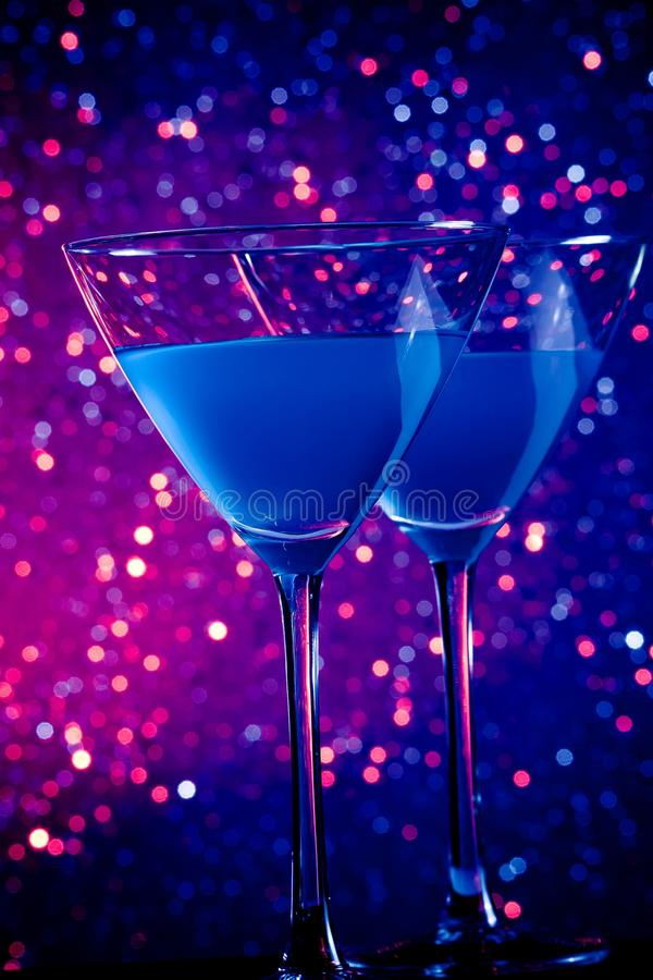 A pair of glasses of blue cocktail on table. A pair of glasses of blue cocktail on blue and violet tint light bokeh background royalty free stock photos