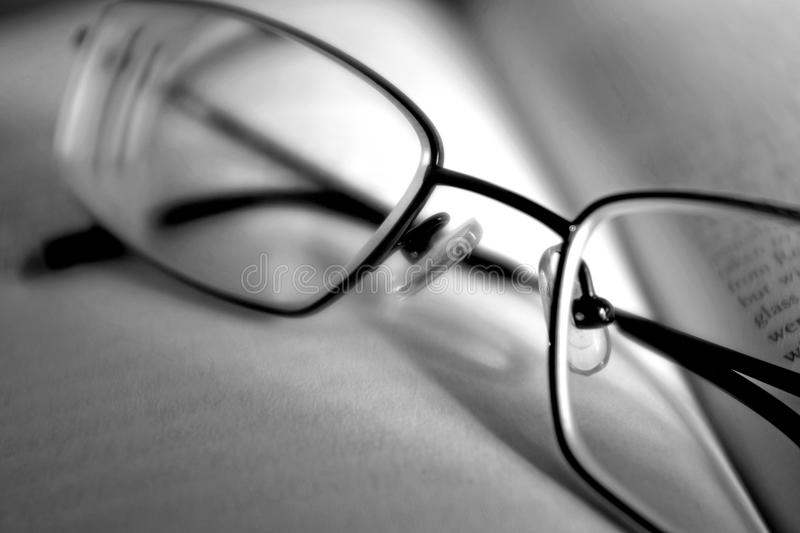 A pair of glasses on a book in black and white stock image
