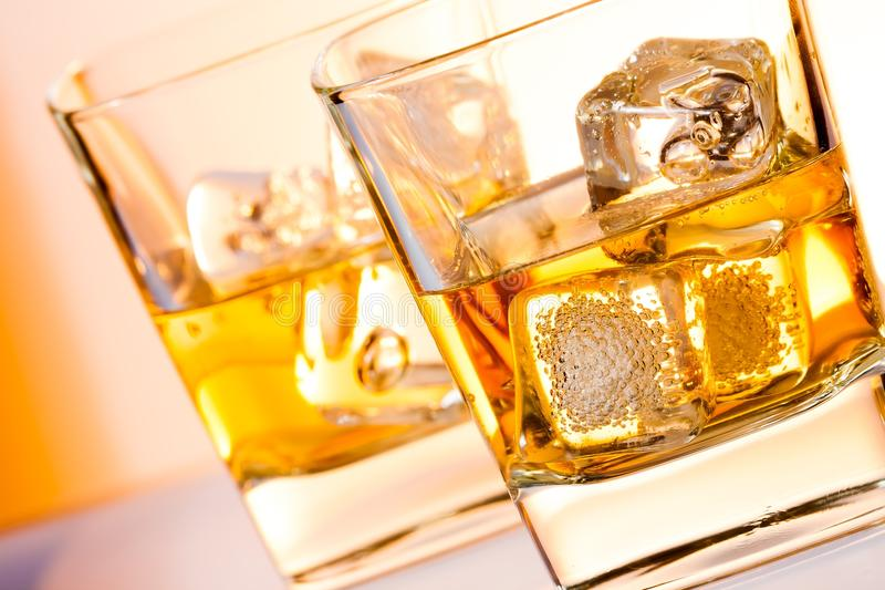 A pair of glasses of whisky with ice. On white bar table royalty free stock image