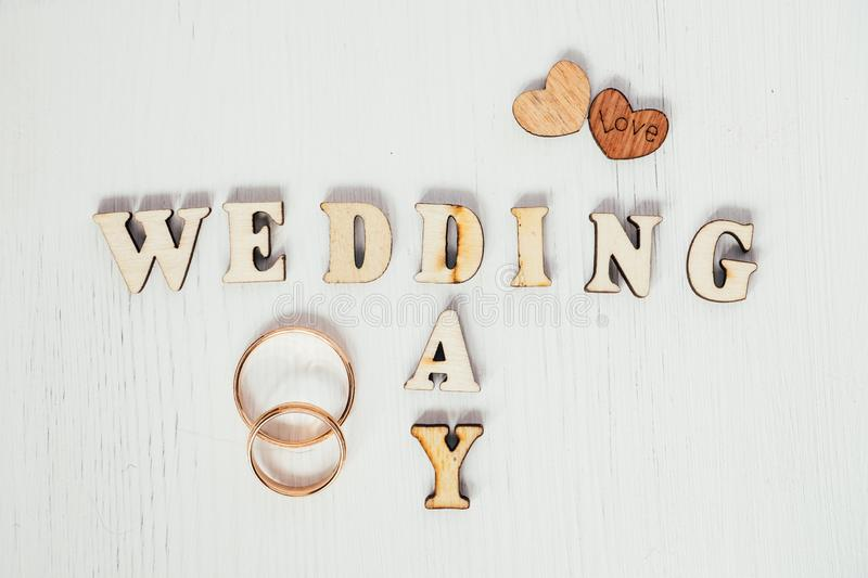 Pair gold rings with two wooden hearts and inscription wedding day on white background. Pair gold male and female rings with two brown wooden hearts and folded stock photo