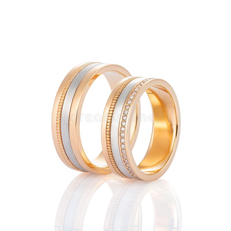 Pair of gold wedding ring with diamonds isolated on white background. Pair of rose gold and white gold wedding ring with diamonds isolated on white background royalty free stock image
