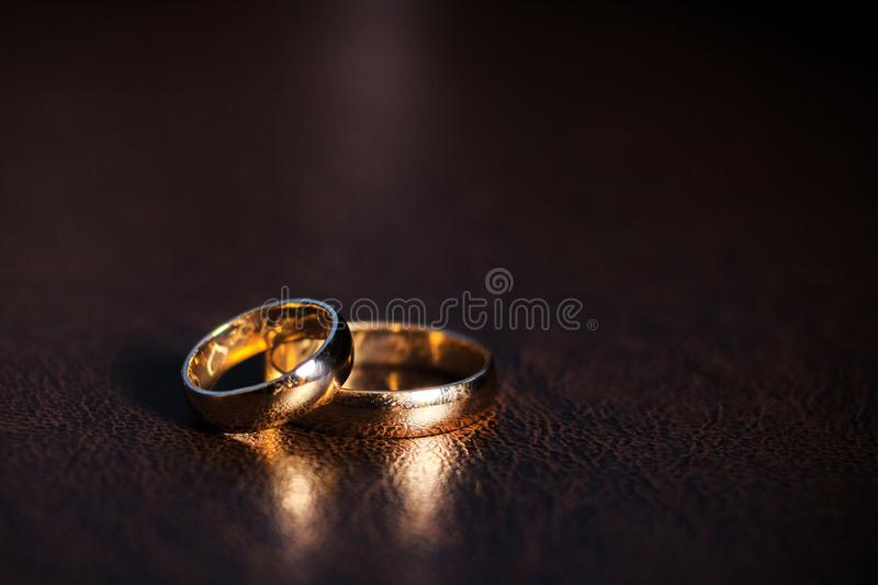 A pair of gold wedding rings, classic gold rings, on a dark background royalty free stock photo