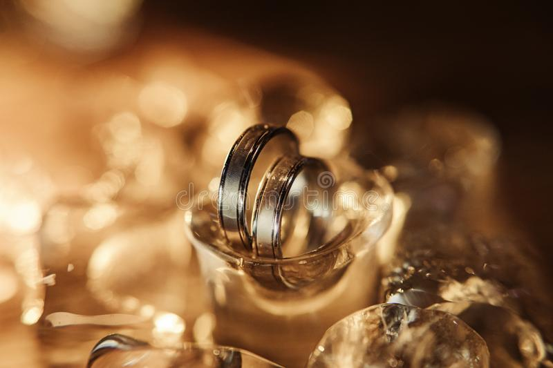 pair of gold wedding rings on ice cubes sparkle and reflection royalty free stock photos