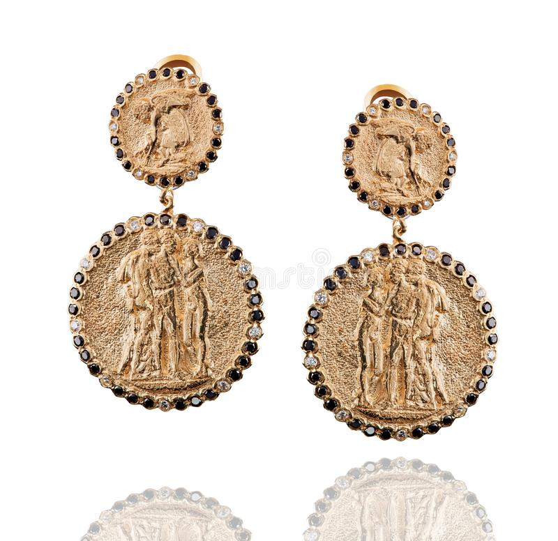 A pair of golden coins earrings with black and white diamonds stock photo