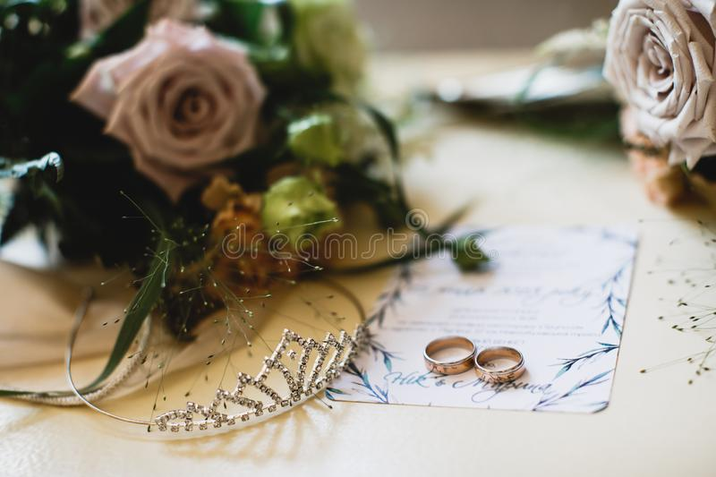 Pair of a golden rings and a tiara are laying on the table. There are wedding invatation and flower bouquets near them.  royalty free stock image