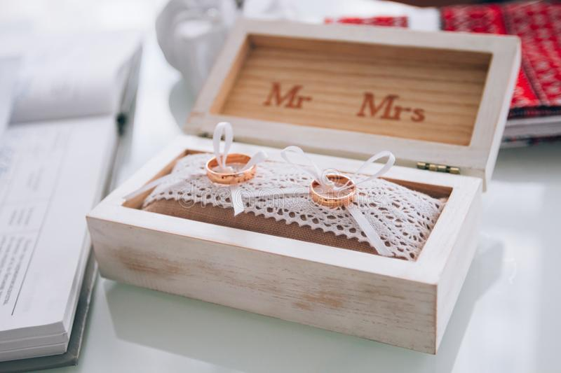 A pair of golden wedding rings lying in a white wooden box. Wedding decoration. Symbol of family, unity and love.  stock image