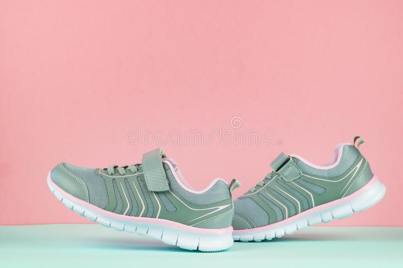 A pair of gray walking sneakers on a blue floor on a pink background. Sports shoes royalty free stock photography