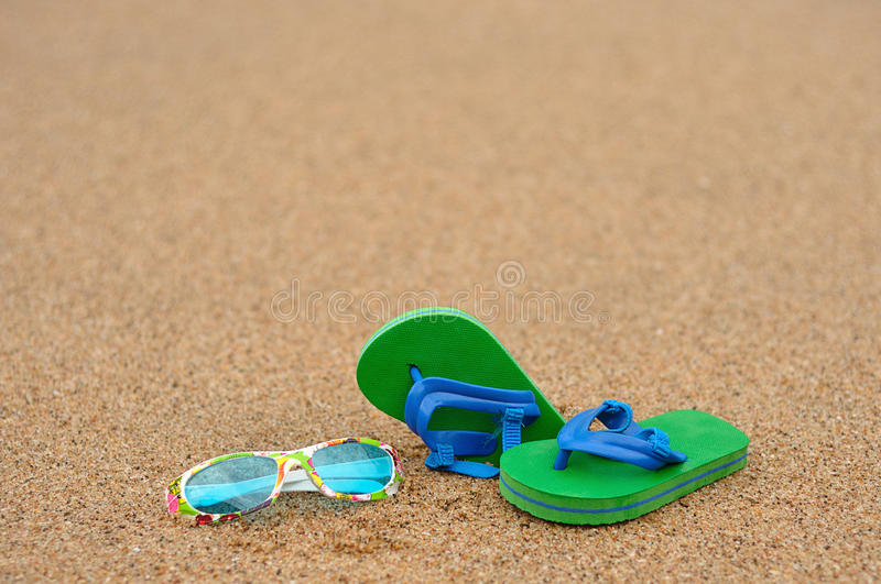 A pair of green and blue flip flops with colorful sunglasses royalty free stock image