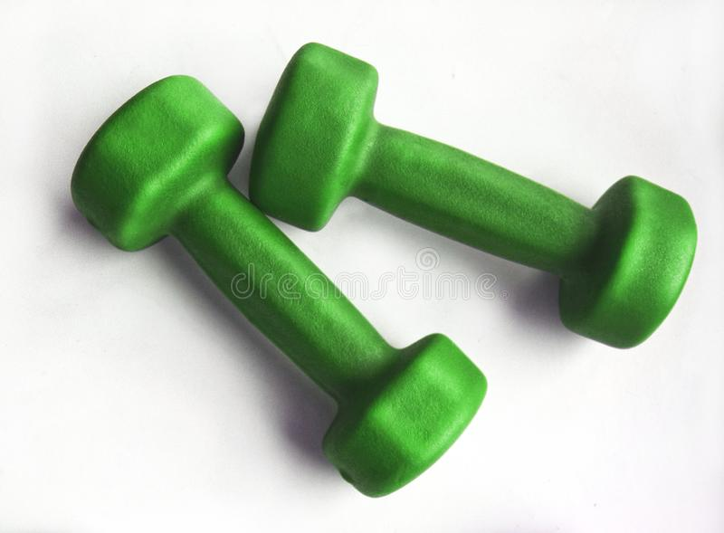 Pair of green fitness dumbbells stock photography
