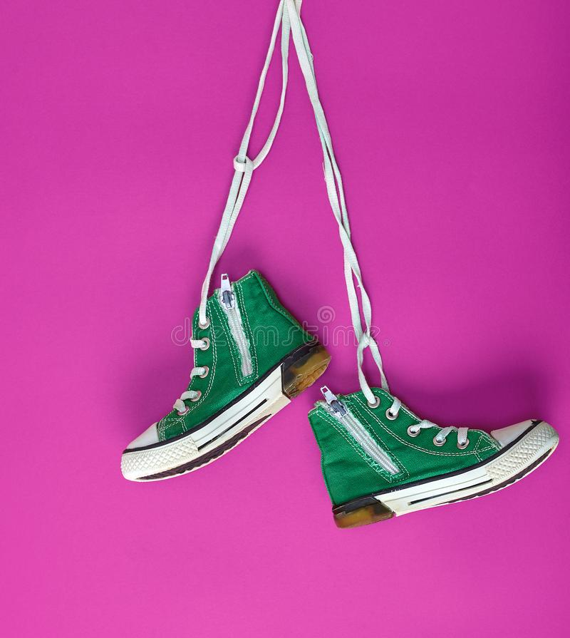 Pair of green textile sneakers on white lace. Pair of green textile sneakers hanging on bella lace, pink background stock photos