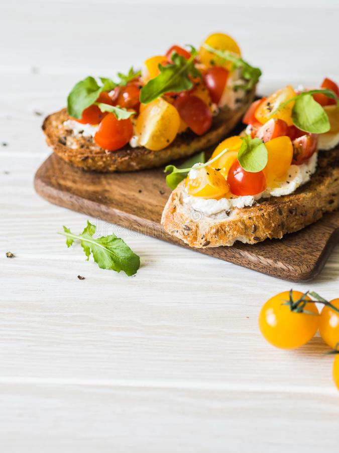 Pair of grilled toasts with cream cheese and slices of fresh tomatoes of various colors with fresh arugula and ground black pepper. On wooden cutting board stock images