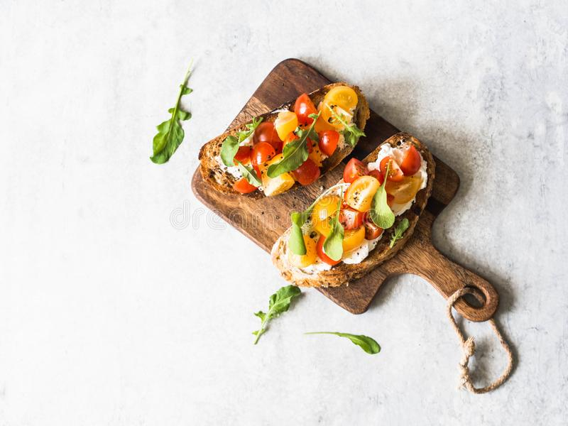 Pair of grilled toasts with cream cheese and slices of fresh tomatoes of various colors with fresh arugula and ground black pepper. On wooden cutting board stock image