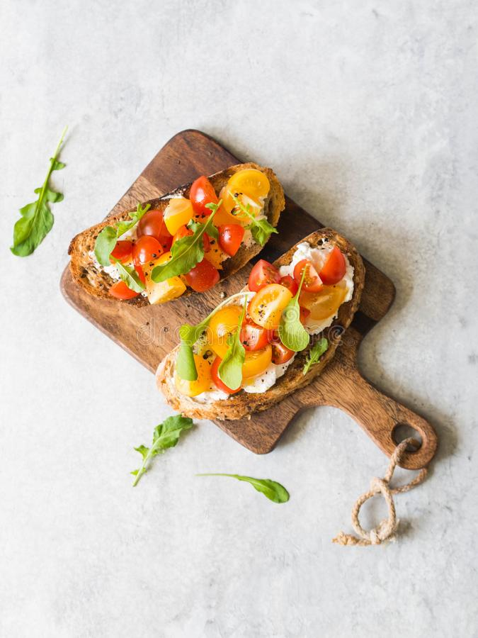 Pair of grilled toasts with cream cheese and slices of fresh tomatoes of various colors with fresh arugula and ground black pepper. On wooden cutting board royalty free stock photo