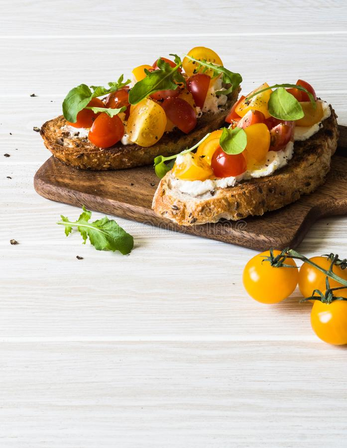 Pair of grilled toasts with cream cheese and slices of fresh tomatoes of various colors with fresh arugula and ground black pepper. On wooden cutting board stock photos