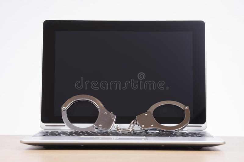 Pair of handcuffs against a blank laptop screen stock image