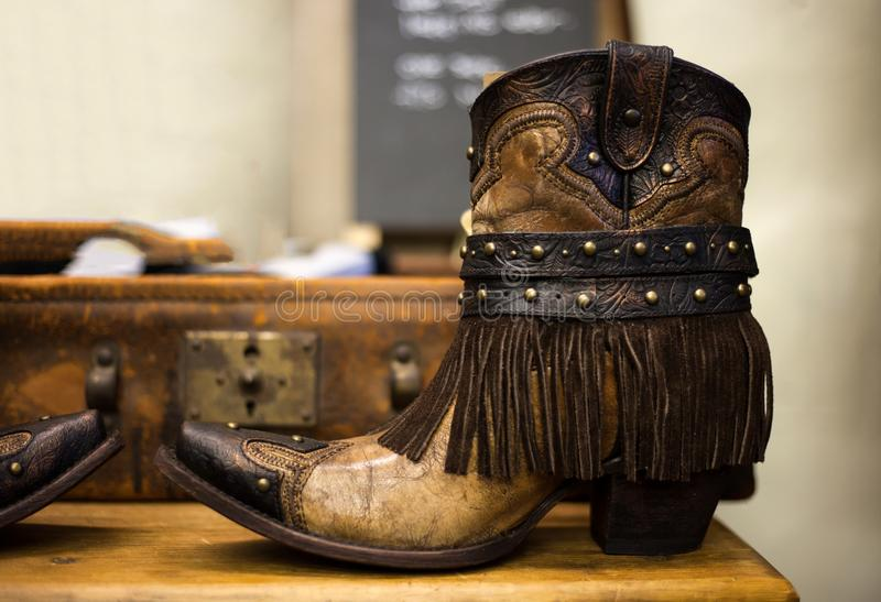 Pair of handmade brown leather cowgirl boots with vintage suitcase in background stock photo