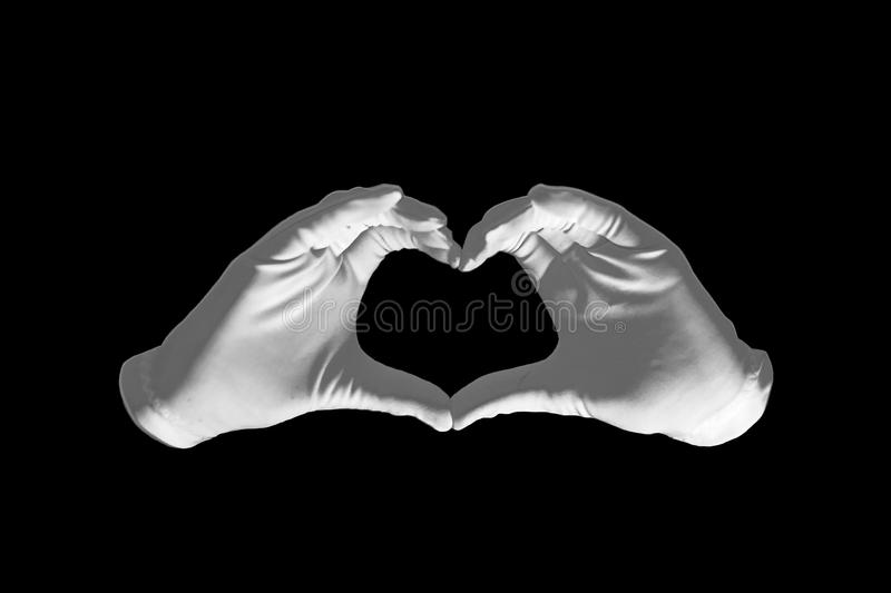 Pair of hands in the form of heart on a black background. love and relationships concept - closeup of hands showing heart shape.  royalty free stock photo