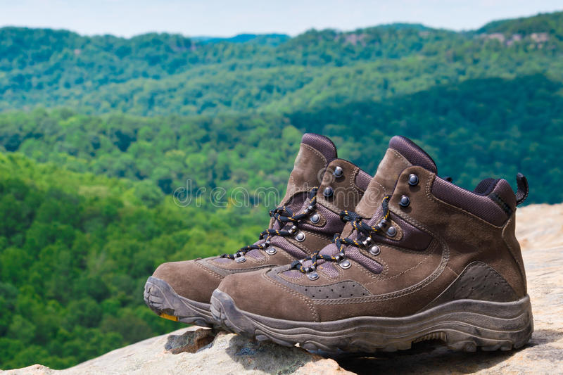 Pair of hiking boots in front of mountain forest. Landscape. selective focus, shallow dof royalty free stock image