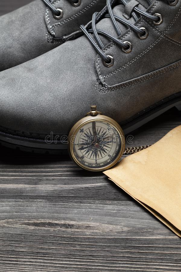 Pair of hiking boots, handmade paper sheet and vintage compass on wooden table stock images