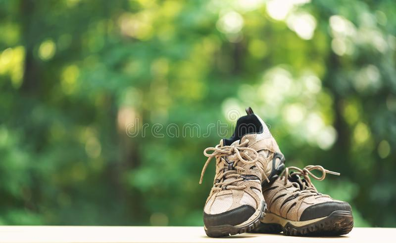 Pair of hiking boots. On a shiny green forest background stock image