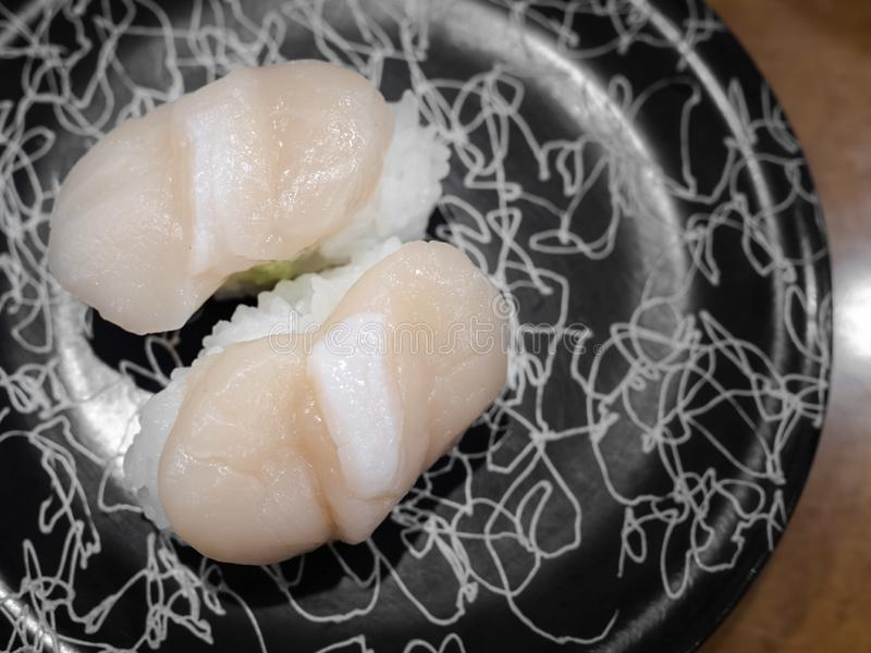 A pair of Hotate sushi, Japanese raw scallop meat on rice. On black plate royalty free stock images