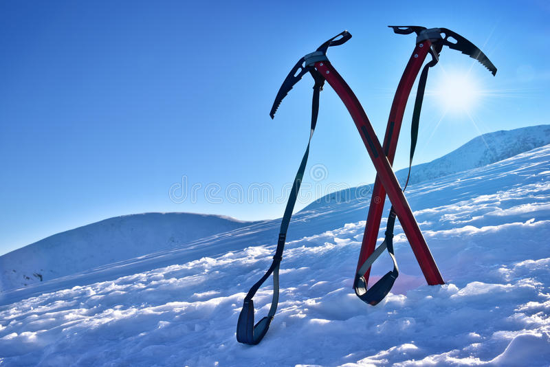 Pair of ice axes on mountain slope. In winter stock photo