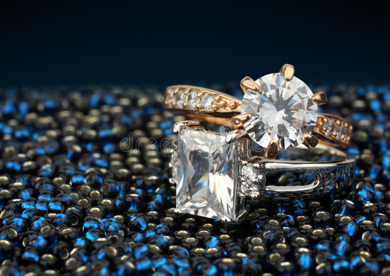 Pair of jewelry rings with big diamonds on dark blue background stock images