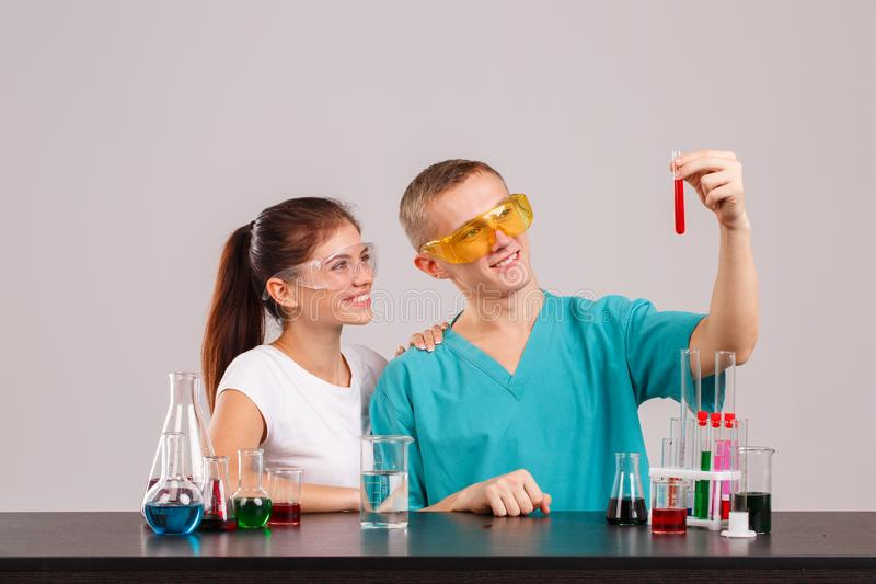 A pair assistants, holding a glass flask with a red liquid and looking at it. Indoors laboratory. Isolation. A pair of laboratory assistants in uniform and royalty free stock images