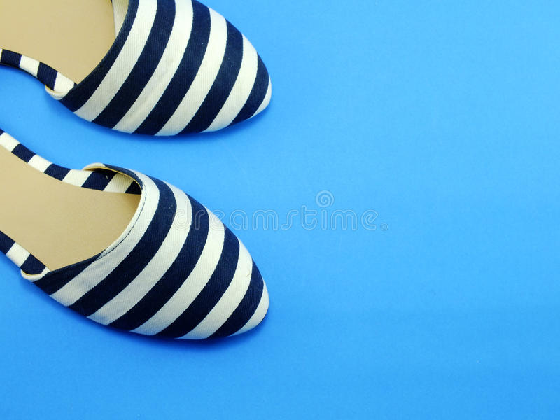 Pair ladies flat shoes. Ballerina ladies shoes on blue background stock image