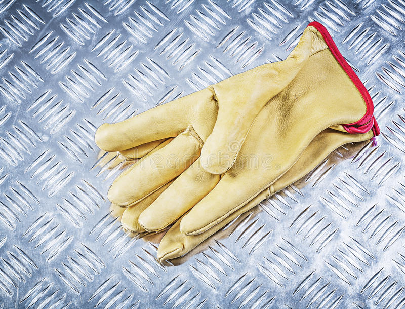 Pair of leather working gloves on corrugated metal plate directl. Y above construction concept royalty free stock photography