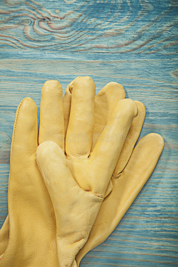 Pair of leather working gloves on wooden board construction conc. Ept royalty free stock image