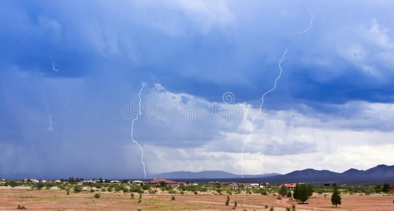A Pair of Lightning Strikes Above a Rural Neighborhood royalty free stock photo