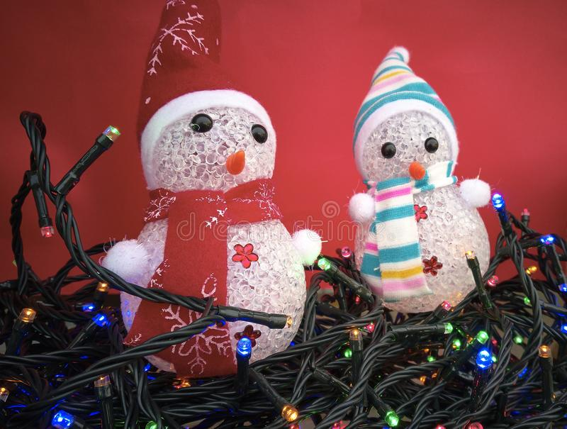 The symbol of Christmas. Pair of little snowmen to be used as Christmas decorations immersed in a sea of colored Christmas lights royalty free stock photography