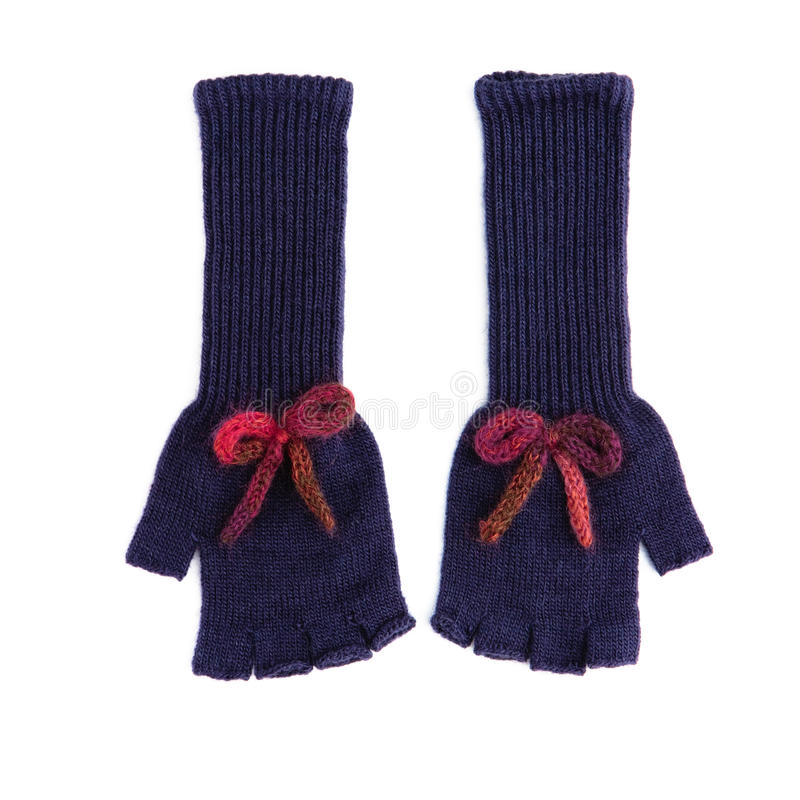 Pair of long dark blue fingerless woolen gloves. With red bows on white background royalty free stock image