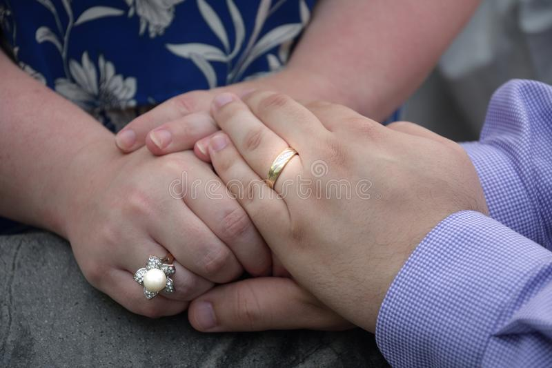 A pair of lovers hands wearing wedding rings and touching royalty free stock image
