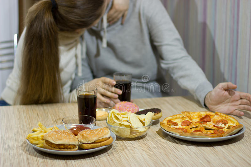 A pair of lovers sit at the table and eat fast food. Unhealthy concept stock photography