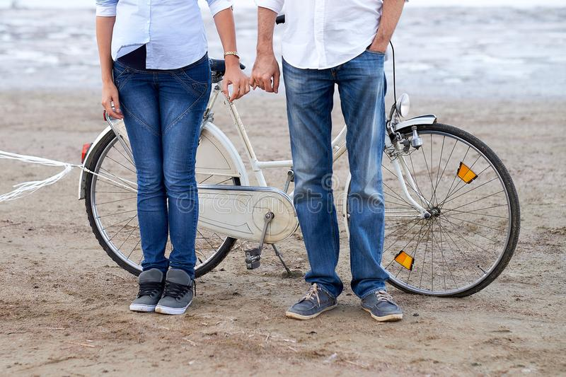 A pair of lovers spending time on the ocean. Man and girl rides a bicycle royalty free stock photography
