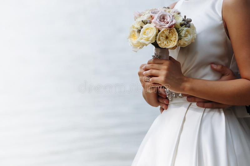 A pair of loving newlyweds hold hands royalty free stock image